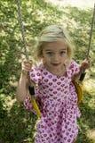 Little child blond girl having fun on a swing outdoor. Summer playground Stock Photos