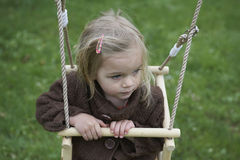 Little child blond girl having fun on a swing outdoor. Summer playground Royalty Free Stock Photography