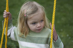 Little child blond girl having fun on a swing outdoor. Summer playground Stock Photography