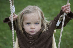 Little child blond girl having fun on a swing outdoor. Summer playground Stock Images