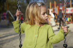 Little child blond girl having fun on a swing outdoor. Summer playground Stock Image
