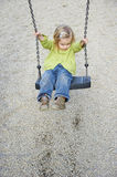 Little child blond girl having fun on a swing outdoor. Summer playground Royalty Free Stock Photos