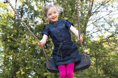Little child blond girl having fun on a swing outdoor. Royalty Free Stock Photos