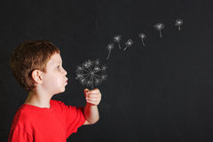Little child blowing dandelion with drawing in blackboard. Little boy blowing dandelion with drawing in blackboard Royalty Free Stock Image