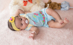 Little child on blue shirt lay down on soft bed with pacifier in royalty free stock images