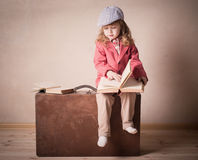 Little child with book on suitcase Stock Photography