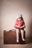 Little child with book on suitcase Stock Photos