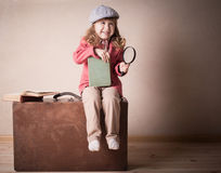 Little child with book on suitcase. Indoor Royalty Free Stock Photos
