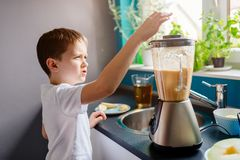 Little child boy adding piece of melon to blender Royalty Free Stock Photos