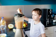 Little child boy adding piece of melon to blender Royalty Free Stock Photography