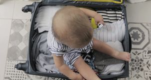 Little child boy age1 playing in a travel suitcase. Little child boy age 1 year playing at home a kid traveler game in a travel suitcase. Children travel stock footage