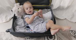 Little child boy age1 playing in a travel suitcase. Little child boy age 1 year playing at home a kid traveler game in a travel suitcase. Children travel stock video