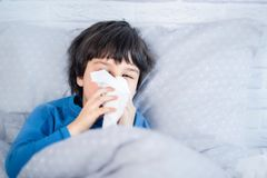 Little child boy blow his nose. Sick child with napkin in bed. Allergic kid, flu season. Kid with cold rhinitis, get cold royalty free stock photography
