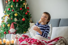 Little child, boy, blowing his nose and sneezing, lying sick in Stock Image