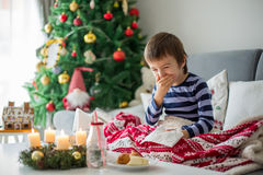 Little child, boy, blowing his nose and sneezing, lying sick in. Bed on Christmas royalty free stock photography