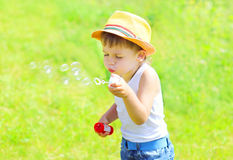 Little child  boy blowing soap bubbles outdoors in summer Royalty Free Stock Photography