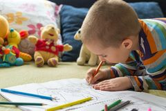 Little child boy drawing with color pencils. Children`s creativity. Boy sitting on the bed and drawing on coloring book with color pencils Stock Photography
