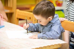 Little child boy drawing with colorful pencils in preschool at table in kindergarten Stock Photos