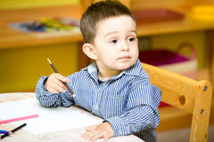 Little child boy drawing with colorful pencils in preschool at  table in kindergarten Royalty Free Stock Photography