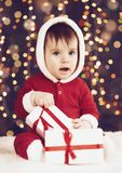 Little child boy dressed as santa playing with christmas decoration, dark background with illumination and boke lights, winter hol. Iday concept Royalty Free Stock Photo