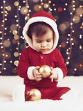 Little child boy dressed as santa playing with christmas decoration, dark background with illumination and boke lights, winter hol Stock Photography