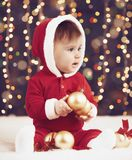 Little child boy dressed as santa playing with christmas decoration, dark background with illumination and boke lights, winter hol. Iday concept Royalty Free Stock Photos