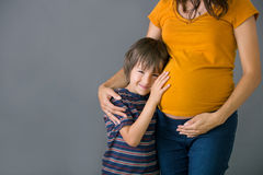 Little child, boy, hugging his pregnant mother at home, isolated. Image, copy space. Family concept Royalty Free Stock Photo