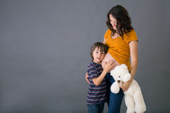 Little child, boy, hugging his pregnant mother at home, isolated Stock Images