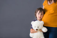 Little child, boy, hugging his pregnant mother at home, isolated Royalty Free Stock Image