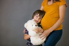 Little child, boy, hugging his pregnant mother at home, isolated Stock Photo