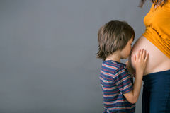 Little child, boy, hugging his pregnant mother at home, isolated. Image, copy space. Family concept Royalty Free Stock Photos