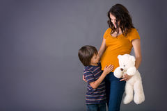 Little child, boy, hugging his pregnant mother at home, isolated Royalty Free Stock Photography