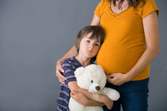 Little child, boy, hugging his pregnant mother at home, isolated. Image, copy space. Family concept Stock Image