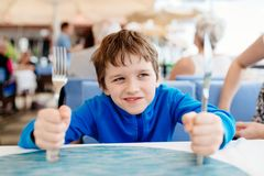 Little child boy hungry waiting for dinner in restaurant Stock Photos