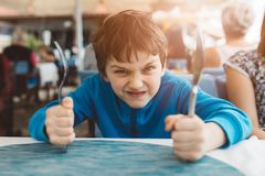 Little child boy hungry waiting for dinner in restaurant Royalty Free Stock Images