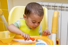 Little child boy learns to eat at the children& x27;s table in the kitchen. Baby eats funny. Little baby eats with a spoon soup. Little child boy learns to eat stock photos