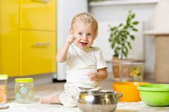Little child boy playing with kitchenware and foodstuffs in domestic kitchen. Child little boy playing with kitchenware and foodstuffs in kitchen royalty free stock images