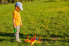 Little child boy playing. Ring throw summer game on a green lawn in the sun. Made of plastic Stock Photo