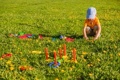Little child boy playing. Ring throw summer game on a green lawn in the sun. Made of plastic Stock Image