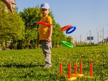 Little child boy playing. Ring throw summer game on a green lawn in the sun. Made of plastic Royalty Free Stock Images