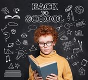 Little child boy reading a book in classroom on chalkboard background.  royalty free stock image