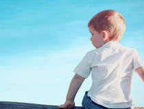 Little child boy sitting pensive looking away outdoors over blue sky on sunset. View from back Stock Image
