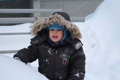 Little baby boy walking in winter in the snow in the yard royalty free stock photos