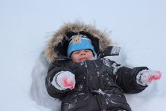 Little child boy walks in winter in the snow in the yard rejoices in the snow royalty free stock image