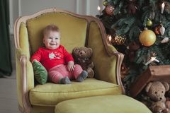 Little child boy wearing red pullover sitting in the vintage armchair by the Christmas tree Royalty Free Stock Photos