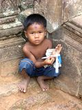 Little child of Cambodia. Throughout many children. on the roads, in cities and here in the ruins of Angkor Wat. They are trying to beg or sell trinkets to Royalty Free Stock Photography