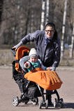 Little child in carriage with mother in city park. Smiling Royalty Free Stock Photography