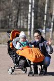 Little child in carriage with mother in city park. Smiling Stock Images