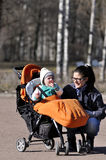 Little child in carriage with mother in city park. Sunday Stock Photo