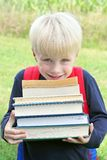 Little Child Carrying Lots of Big Heavy School Books Stock Image